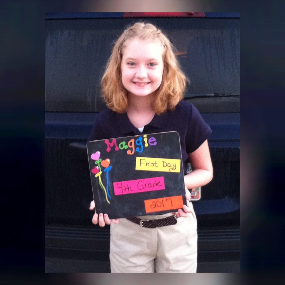 Photo of a young girl holding an arts and crafts project and smiling