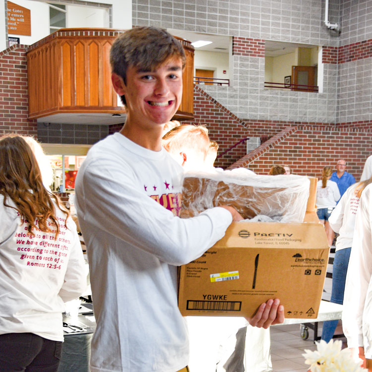 A grinning Student Council guy helping with breakfast