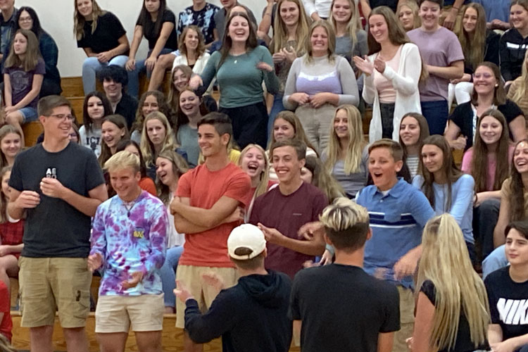 Excited students standing in the bleachers inside the gym